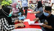 Petugas mendata warga saat vaksinasi COVID-19 keliling di Kebon Kacang, Jakarta, Jumat (9/7/2021). Pemerintah Provinsi DKI Jakarta meluncurkan 16 mobil vaksin COVID-19 keliling guna mempercepat pencapaian target vaksinasi COVID-19 di Ibu Kota. (Liputan6.com/Faizal Fanani)