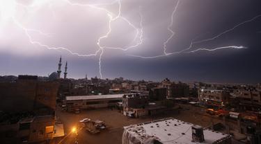 Kilatan petir terlihat saat hujan lebat di atas kota Rafah di Jalur Gaza selatan, Palestina, Kamis (16/1/2020). (AFP/Said Khatib)