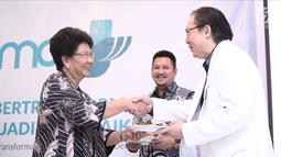 Ketua Yayasan Karya Alpha Omega Non Rawung memberi potongan tumpeng ke Ketua Komite Medik RS EMC Sentul dr Sendjaja Muljadi  saat soft launching RS EMC di Sentul, Bogor, Jawa Barat, Sabtu (21/4). (Liputan6.com/Herman Zakharia)