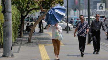 Seorang wanita merapikan payung selama gelombang panas di Jakarta, Selasa (22/10/2019).  BMKG memprediksi wilayah Indonesia akan mengalami panas selama kurang lebih satu minggu ini. Hal ini dikarenakan matahari yang berada dekat dengan jalur khatulistiwa. (Liputan6.com/Faizal Fanani)