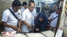 Tim Satgas Pangan Polda Metro Jaya bersama Perum Bulog meninjau harga beras di Pasar Tomang Barat, Jakarta, Rabu (21/11). Kegiatan tersebut bertujuan untuk memantau stabilitas harga beras medium yang dijual di pasaran. (Liputan6.com/Faizal Fanani)