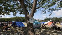 Sebuah jam dinding dipasang di pohon lapangan pengungsian Masjid Agung Daru Salam, Palu, Sulawesi Tengah, Jumat (5/10). Pemindahan dari tenda ke barak pengungsian untuk mempercepat penanganan pengungsi pascagempa.(Www.sulawesita.com)
