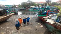Nelayan Cilacap memikul ikan usai melaut. (Foto: Liputan6.com/Muhamad Ridlo)