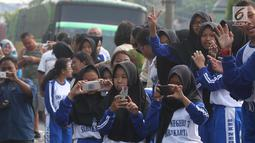 Sejumlah pelajar mengabadikan prosesi kirab kereta kencana pernikahan putri Presiden Jokowi,  Kahiyang Ayu-Bobby Nasution saat menuju Gedung Graha Saba di Surakarta, Rabu (8/11). (Liputan6.com/Angga Yuniar)