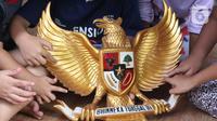 Anak-anak melihat lambang burung Garuda Pancasila di Kampung Pancasila, Karang Tengah, Kota Tangerang, Selasa (1/6/2021). Kegiatan tersebut antara lain seperti gotong royong membersihkan kampung dan sosialisasi penanaman nilai Pancasila kepada warga . (Liputan6.com/Angga Yuniar)