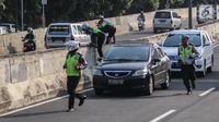Petugas polisi lalu lintas (polantas) mengejar pengendara sepeda motor  yang melintasi JLNT Kampung Melayu-Tanah Abang, Jakarta, Selasa (25/7). Sepeda motor dilarang melintas di JLNT tersebut karena merupakan jalur cepat. (Liputan6.com/Faizal Fanani)