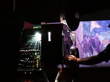 Teknisi mengoperasikan proyektor film layar tancap di kawasan Sawangan, Depok, Jawa Barat, Sabtu (11/7/2020). Layar tancap atau bioskop terbuka menjadi alternatif bagi warga untuk menikmati film di tengah penerapan new normal di kawasan Jabodetabek. (Liputan6.com/Herman Zakharia)
