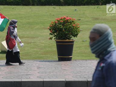 Peserta aksi berjalan di sekitar halaman Monumen Nasional, Jakarta, Jumat (11/5). Ribuan umat muslim melakukan aksi menyoroti konflik Palestina dan Israel pada perebutan bangunan suci atau Baitul Maqdis di Yerusalem. (Liputan6.com/Helmi Fithriansyah)