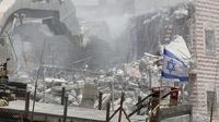 Bendera Israel terlihat selama penghancuran bangunan Palestina di daerah Wadi al-Hummus yang berdekatan dengan Palestina (22/7/2019). Palestina menuduh Israel menggunakan keamanan sebagai dalih untuk mengusir mereka dari Tepi Barat. (AFP Photo/Ahmad Gharabli)