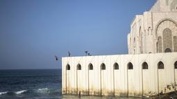 Seorang pria melompat untuk menyelam ke Samudra Atlantik dari dinding masjid Hassan II di Casablanca, Maroko (7/2/2020). Masjid ini memiliki minaret yang paling tinggi di dunia dengan ketinggian 210 meter (689 kaki) dan memiliki kapasitas 25.000 orang. (AP Photo/Mosaab Elshamy)