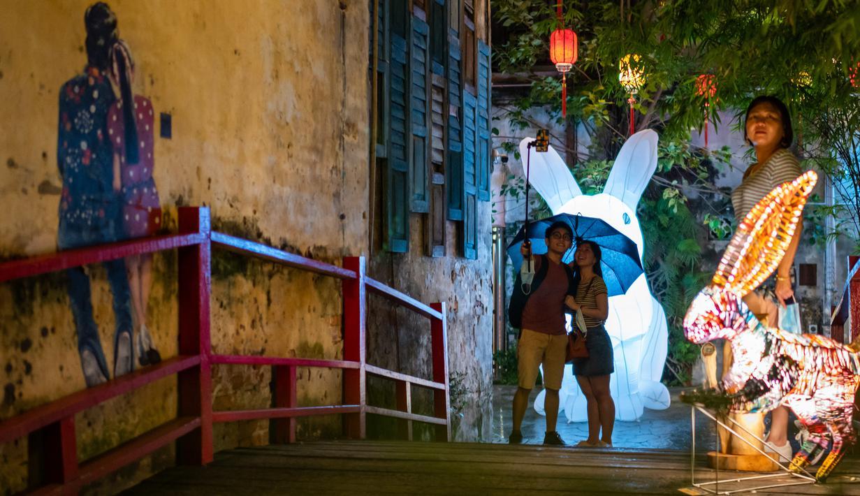 Warga berswafoto di depan instalasi Jade Rabbit di Kwai Chai Hong, Kuala Lumpur, Malaysia, 25 September 2020. Delapan desain unik instalasi seni Jade Rabbit dipamerkan di Kwai Chai Hong dalam sebuah acara untuk merayakan Festival Pertengahan Musim Gugur mendatang. (Xinhua/Zhu Wei)