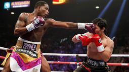 Petinju asal Filipina, Manny Pacquiao menghindari pukulan petinju AS, Adrien Broner selama pertandingan tinju kelas welter WBA di Las Vegas (19/1). Pacquiao  menang lewat kemenangan angka mutlak, 117-111, 116-112, dan 116-112. (AP Photo/John Locher)