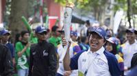 Legenda tinju Indonesia, Ellyas Pical membawa obor saat Torch Relay Asian Games 2018 di Kota Bogor, Jawa Barat, Selasa (14/8/2018). (Bola.com/Reza Bachtiar)