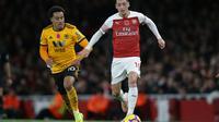 Aksi Mesut Ozil saat mengiring bola kontra Wolverhampton pada laga lanjutan Premier League, yang berlangsung Minggu (11/11) di stadion Emirates. Arsenal ditahan imbang Wolverhampton 1-1. (AFP/Daniel Olivas)