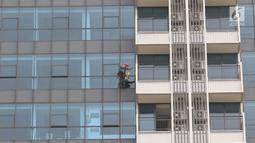 Pekerja membersihkan kaca gedung di Jakarta, Kamis (18/10). Kepesertaan BPJS Ketenagakerjaan tahun 2018 sebanyak 29,6 juta peserta aktif, atau tumbuh 12,9% dari jumlah peserta aktif tahun 2017 sebanyak 26,2 juta peserta. (Liputan6.com/Immanuel Antonius)