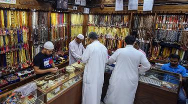 Dua pria membeli tasbih selama bulan suci Ramadan di sebuah pasar di Kota Kuwait (25/5/2019). Kuwait adalah negara monarki yang kaya akan minyak di pesisir Teluk Persia, Timur Tengah. (AFP Photo/Yasser Al-Zayyat)