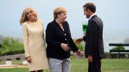 Presiden Prancis Emmanuel Macron (kanan) dan istrinya Brigitte Macron (kiri) menyambut Kanselir Jerman Angela Merkel (tengah) yang tiba di KTT G7, Biarritz, Prancis, Sabtu (24/8/2019). KTT G7 ini berlangsung selama tiga hari di resor tepi laut Atlantis. (Sean Kilpatrick/The Canadian Press via AP)