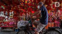 Pesepeda melintas di depan penjual pernak-pernik Imlek di Kawasan Petak Sembilan, Glodok, Jakarta, Minggu (7/2/2021). Tahun ini perayaan Hari Raya Imlek jatuh pada tanggal 12 Februari 2021 mendatang. (Liputan6.com/Johan Tallo)