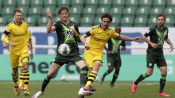 Pemain Borussia Dortmund, Thomas Delaney, melepaskan tendangan saat pertandingan melawan Wolfsburg pada laga Bundesliga, Minggu (24/5/2020). Borussia Dortmund menang 2-0 atas Wolfsburg. (AP/Michael Sohn)