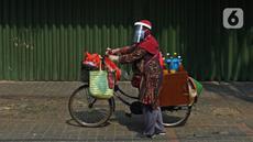 Tidar (46), mengayuh saat berjualan jamu di Pasar Baru, Jakarta, Kamis (11/06/2020). Penjual jamu tradisional keliling ini tampak mematuhi protokol kesehatan pencegahan COVID-19 dengan mengenakan masker, face shield, dan sarung tangan dalam melayani pelanggan setianya. (Liputan6.com/Herman Zakharia)