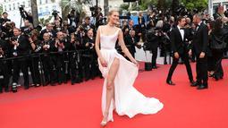 Model Toni Garrn berpose di karpet merah saat tiba menghadiri pemutaran perdana film 'A Hidden Life' di festival film internasional ke-72, Cannes, Prancis selatan (19/5/2019). Model 26 tahun asal Jerman ini tampil memesona berbalut gaun putih dengan belahan paha terbuka. (AP Photo/Vianney Le Caer)