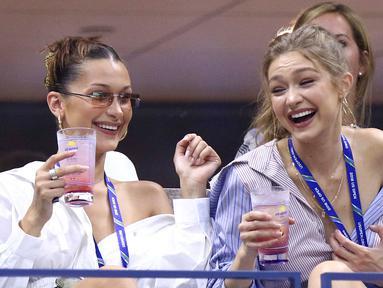 Supermodel Gigi Hadid dan sang adik, Bella Hadid (kiri) menyaksikan perempat final tunggal putri antara petenis AS, Serena Williams melawan Karolina Pliskova dari Ceko pada hari ke-9 turnamen AS Terbuka di New York, Selasa (4/9). (Greg Allen/Invision/AP)