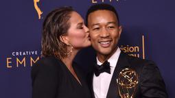 Chrissy Teigen mencium John Legend selama Creative Arts Emmy 2018 di Microsoft Theater di Los Angeles, California, AS (9/9). Penghargaan ini untuk artis yang telah memenangkan di Emmy, Grammy, Oscar, dan Tonys. (AFP Photo/Alberto E. Rodriguez)