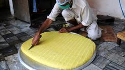 Seorang pria membuat penganan manis tradisional di hari raya Idul Fitri di Peshawar, Pakistan barat laut, pada 25 Mei 2020. Warga Pakistan memiliki tradisi memakan penganan manis saat merayakan Idul Fitri, yang menandai akhir bulan puasa Ramadan. (Xinhua/Saeed Ahmad)