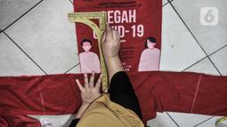 Siti Zahro (44) menyelesaikan pembuatan celemek dari tas bansos Covid-19 di industri jahit rumahan KG-Lupe Fashion, Salemba, Jakarta, Senin (16/11/2020). Siti berinovasi membuat celemek berbahan tas bansos Covid-19 yang didapat dari pemerintah selama PSBB. (merdeka.com/Iqbal S. Nugroho)