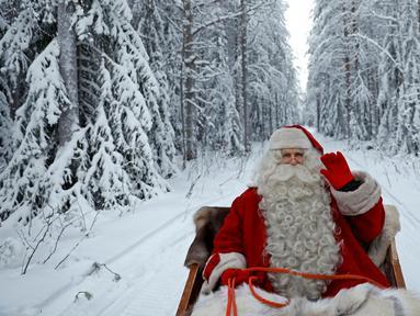 Santa Claus di atas kereta hadiahnya untuk mempersiapkan perayaan Natal di Lingkar Arktik, dekat Rovaniemi, Finlandia, 15 Desember 2016. Setiap tahunnya, desa yang mendapat julukan Desa Sinterklas ini ramai oleh wisatawan. (REUTERS/Pawel Kopczynski)