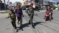 Prajurit Marinir TNI AL membantu warga menyeberangi jalan di perempatan lampu merah kota Palu pascagempa dan tsunami di Palu, Sulawesi Tengah, Jumat (5/10). Selain berjaga di jalan, mereka juga berjaga di beberapa ruko di Palu. (Liputan6.com/Fery Pradolo)