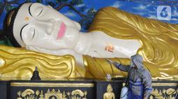 Petugas menyemprotkan cairan disinfektan ke patung Buddha tidur raksasa di Vihara Buddha Dharma dan 8 Posat, Bogor, Jawa Barat, Minggu (7/2/2021). Patung buddha tidur raksasa sepanjang 18 meter dan tinggi 5 meter tersebut dibersihkan setiap tahun menjelang Tahun Baru Imlek. (merdeka.com/Arie Basuki)