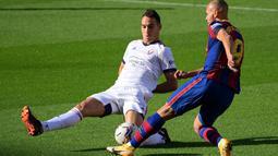 Bek Osasuna, Unai Garcia (kiri) berebut bola dengan pemain depan Barcelona, Martin Braithwaite pada pekan ke-11 Liga Spanyol 2020-2021di stadion Camp Nou, Minggu (29/11/2020). Barcelona berhasil pesta gol 4-0 saat menjamu Osasuna. (LLUIS GENE / AFP)