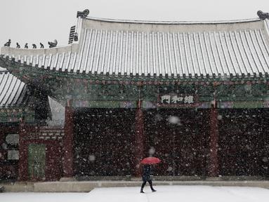 Seorang wanita menggunakan payung  berjalan saat hujan salju di Istana Gyeongbok di Seoul, Korea Selatan (13/12). Istana Gyeongbok merupakan kerajaan utama selama Dinasti Joseon dan salah satu landmark terkenal di kota tersebut. (AFP Photo/Lee Jin-man)