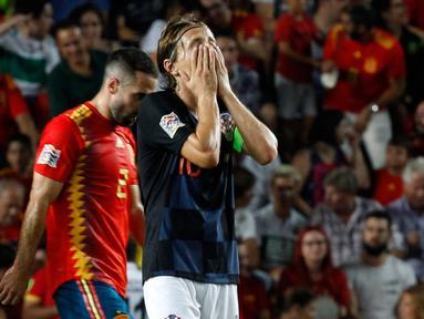 Gelandang Kroasia, Luka Modric menutupi wajahnya setelah bek Spanyol, Sergio Ramos mencetak gol kelima selama pertandingan UEFA Nations League di stadion Manuel Martinez Valero, Spanyol (11/9). Spanyol menang 6-0 atas Kroasia. (AP Photo/Alberto Saiz)