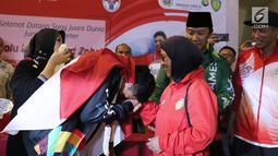 Pelari muda Indonesia, Lalu Muhammad Zohri (kiri) mencium tangan pelatih pelatnas, Eni Nuraini saat penyambutan di Terminal 3 Bandara Soetta, Tangerang, Selasa (17/7). Lalu M Zohri meraih emas lari 100m putra U-20 IAAF. (Liputan6.com/Helmi Fithriansyah)