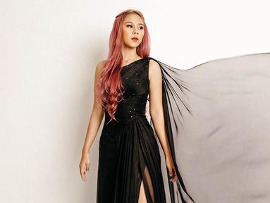 Dalam salah satu unggahannya di Instagram, Nadin Amizah tampil dengan dress hitam panjang dan rambut pink-nya (Liputan6.com/IG/@cakecaine)