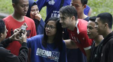 Pemain Arema FC, Pavel Smolyachenko, foto bersama fans usai sesi latihan di Stadion Gajayana, Malang, Kamis (11/4). Setelah sesi latihan, pemain Arema FC melayani permintaan fans untuk foto bersama. (Bola.com/Yoppy Renato)