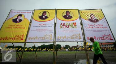 Seorang pekerja melintasi baliho Ade Komarudin di kawasan alun alun utara Yogyakarta, Jumat (11/3/2016). Ade Komarudin akan mendekalrasikan pencalonan ketua Umum DPP Golkar yang akan bertarung pada Munaslub 2016. (Liputan6.com/Boy Harjanto)