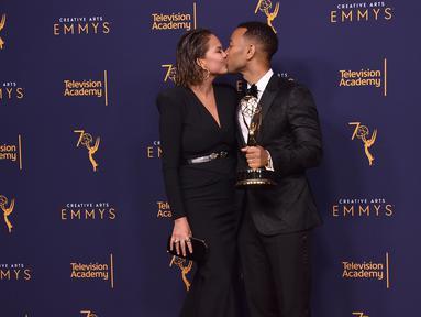 Chrissy Teigen dan John Legend berciuman di karpet merah selama Creative Arts Emmy 2018 di Microsoft Theater di Los Angeles, California, AS (9/9). John Legend mendapatkan penghargaan di acara tersebut. (AFP Photo/Alberto E. Rodriguez)