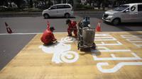 Pekerja mengecat rambu jalur kuning khusus sepeda motor di Jalan Medan Merdeka, Jakarta, Selasa (16/1). Penerapan jalur kuning sepeda motor di kawasan tersebut akan dimulai per 15 Januari 2018. (Liputan6.com/Arya Manggala)