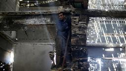 Seorang pria Palestina membantu seniman asal Belanda, Marjan Teeuwen, menciptakan sebuah karya arsitektur dari reruntuhan rumah yang hancur bekas perang pada 2014 di Khan Younis, selatan Jalur Gaza, 12 November 2016. (REUTERS/Ibraheem Abu Mustafa)