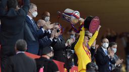 Striker Barcelona, Lionel Messi, mengangkat trofi usai menjuarai Copa del Rey di Stadion Olimpico de Sevilla, Minggu (18/4/2021). Barcelona menang 4-0 atas Athletic Bilbao. (AFP/Cristina Quicler)
