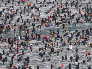 Peserta saat mengikuti lomba memancing ikan trout di sungai yang membeku di Hwacheon, Korea Selatan (6/1). Kontes ini merupakan bagian dari festival es tahunan yang menghasilkan lebih dari 1.000.000 pengunjung setiap tahunnya. (AP Photo/Ahn Young-joon)