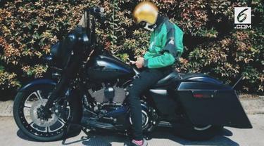 Seorang driver ojek online menggunakan motor Harley untuk mengantar pesanan penumpang.