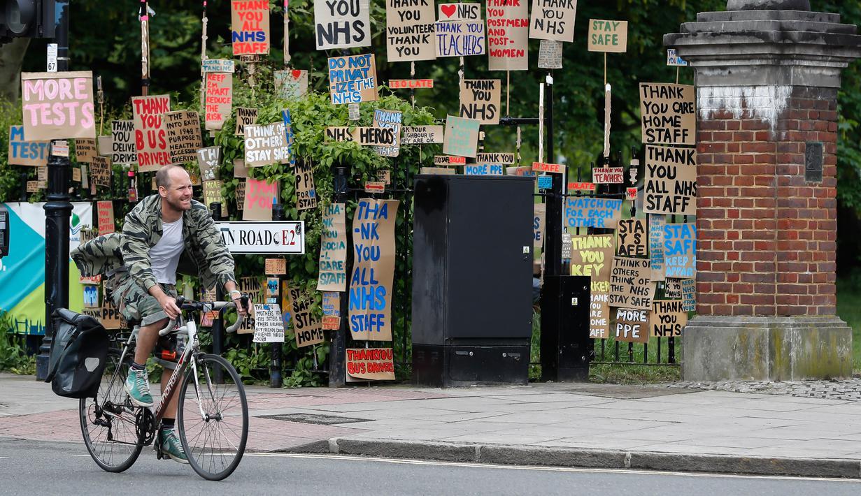 Seorang pria berjalan melewati kumpulan plakat yang dirancang oleh seniman lokal Peter Liversidge untuk mendukung Layanan Kesehatan Nasional (National Health Service/NHS) di London, Inggris, (29/4/2020). (Xinhua/Han Yan)