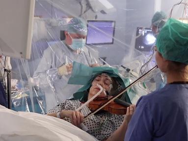 Gambar yang direkam pada 31 Januari 2020, musisi Dagmar Turner bermain biola saat berlangsungnya operasi pengangkatan tumor otak di King's College Hospital, London. Ini dilakukan untuk mempertahankan keahlian Turner dalam bermain biola, hobinya sejak usia 10 tahun. (KING'S COLLEGE HOSPITAL/AFP)