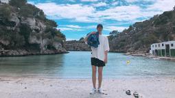 Pria yang pernah bermain dalam drama The Heirs saat liburan di pantai juga terlihat santai. Ia memilih untuk mengenakan kaus oversized berwarna putih yang dipadukan celana pendek serta topi hitam. (Liputan6.com/IG/@actorleeminho)