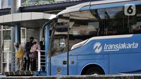 Sejumlah calon penumpang menunggu kedatangan bus Transjakarta di Halte Harmoni, Jakarta, Selasa (16/6/2020). Seiring masa PSBB Transisi, PT Transjakarta menambah waktu operasional dari pukul 05.00-22.00 WIB untuk umum dan hingga 24.00 WIB untuk petugas kesehatan. (merdeka.com/Iqbal Nugroho)