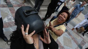Seorang wanita mengenakan helm las untuk melihat gerhana matahari parsial di Mexico City, Senin (21/8). Gerhana matahari total terjadi di 14 negara bagian AS, sementara lainnya mengalami gerhana matahari parsial. (Gustavo Martinez Contreras/AP)